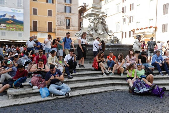 Tourists sit in front of the Pantheon, in Rome, Friday, June 7, 2019.