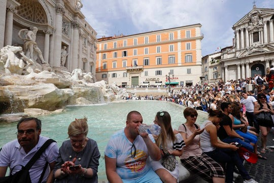 Tourists sit by the Trevi fountain, in Rome, Friday, June 7, 2019.