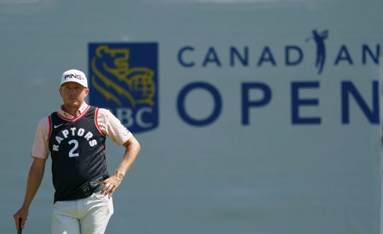Canadian Mackenzie Hughes, wearing a Toronto Raptors Kawhi Leonard jersey, waits to putt on the 13th hole during the first round of the Canadian Open.
