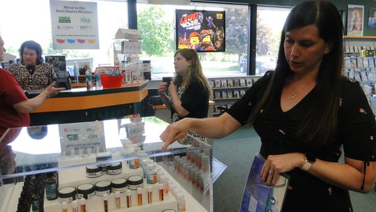 Beth Kerry, Family Video's district manager for Metro Detroit, points out CBD-infused creams and lip balms from Oklahoma-based Natural Native that the movie rental store sells in Waterford Township and 83 other stores in Michigan. More retailers are introducing such products made with hemp, after the federal government legalized the crop in December.