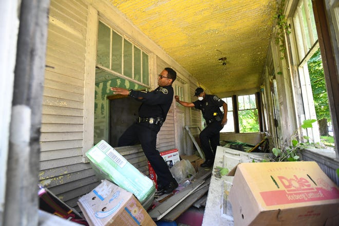 Deputy Chief Todd Bettison and Detroit police officers search abandoned houses Friday, including this one at 17862 Saint Louis in Detroit, in search of additional victims of a serial killer. After the searches, Detroit city workers boarded up the buildings.