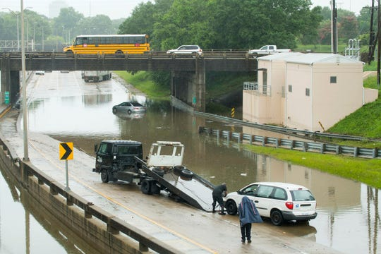 A towing service prepares to hauls out a U.S. Postal Service van from the I-110 southbound curves near the Governor's Mansion, as a result of flash flooding from heavy rains.