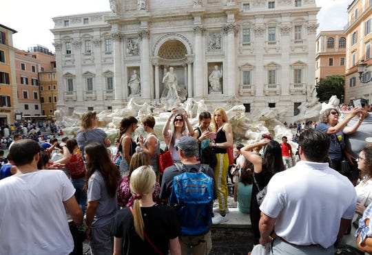Tourists gather in front of the Trevi fountain, in Rome, Friday, June 7, 2019. Tired of ad hoc bans on ill behavior by tourists, Rome has converted its temporary crackdowns into one big law.