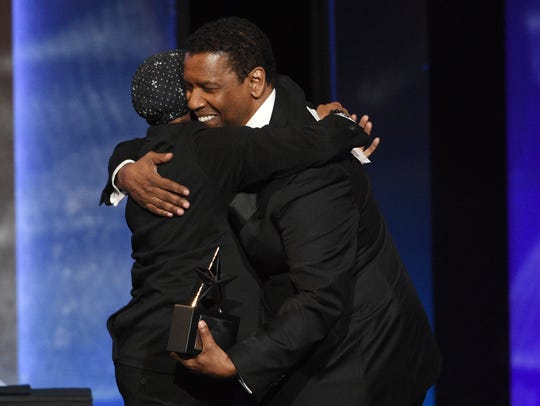 Actor Denzel Washington, right, is embraced by filmmaker Spike Lee as he receives the 47th AFI Life Achievement Award.