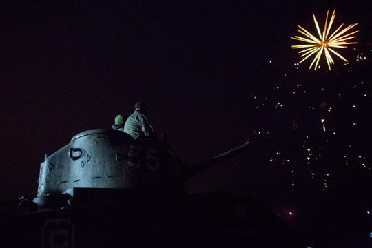 People on a tank watch fireworks in Arromanches in Normandy region of France, Thursday, June 6, 2019.