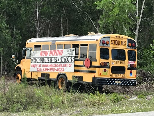 The bus with a banner advertising the need for school bus drivers is parked in front of Lee County Schools Transportation Services.