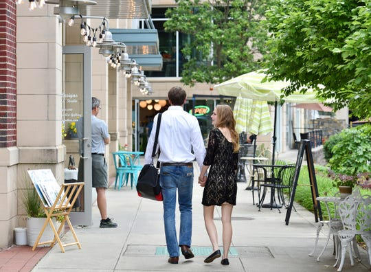 People walk past art studios at Art Crossing in downtown Greenville.