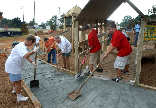 At the under construction addition to Kids Planet in Greer, volunteers from left, Susan Burch, Meredith Wally, Bob Tomlinson and his sons Alex, 12, and Ben, 12, work putting in stone dust for handicapped accessible walkways. Alex and Ben were there representing Boy Scout Troop 260, they said. File photo by Owen Riley Jr. 10-5-01