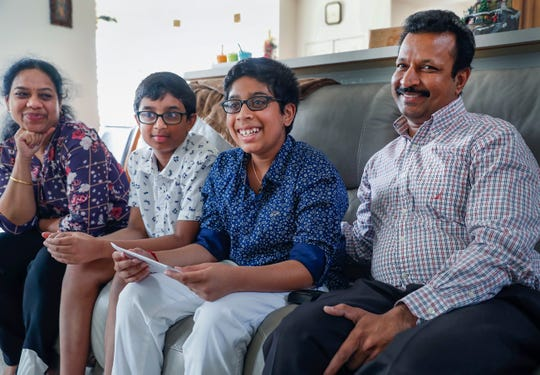Akul Chinthala,13, smiles after reading a letter he wrote to the family who donated a kidney to his father Ramu, right, as his brother Anshul and his mother Aparna, left, look on at their Carmel home on Tuesday, June 4, 2019.