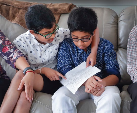 Akul Chinthala,13, holds a letter he wrote to the family who donated a kidney to his father as his brother Anshul looks over his shoulder on at their Carmel home on Tuesday, June 4, 2019.
