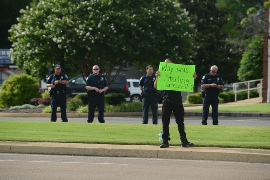 A protester holds a sign asking as four Union City police officers stand behind him at a demonstration demanding answers for the in-custody death of Sterling Higgins on the corner of East Reelfoot Avenue and South First Street in Union City on Thursday, June 6, 2019.