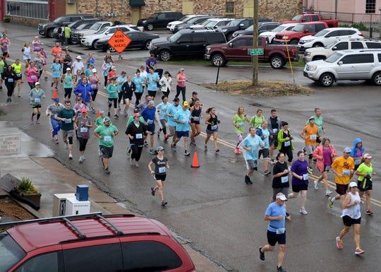 Runners begin the 1-mile run of the Twilight Glow Run on Lafayette Street in Downtown Jackson, Thursday evening, June 6.