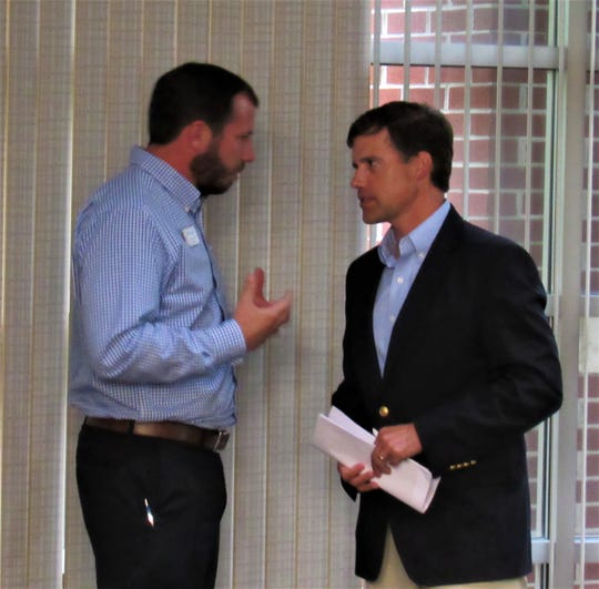 Alderman Drew Burnette confers with Top Golf representative Todd Waldo at the MPC special called meeting on June 6, 2019.