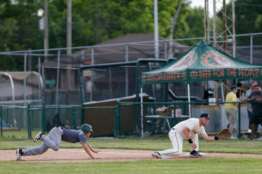 Lafayette Aviators first baseman Chris Monroe (32) leans down for the throw as Danville Dans left fielder Marcel Bachelier (4) slides back into first base during the third inning of a regular season Prospect League baseball game, Thursday, June 6, 2019, at Loeb Stadium in Lafayette.