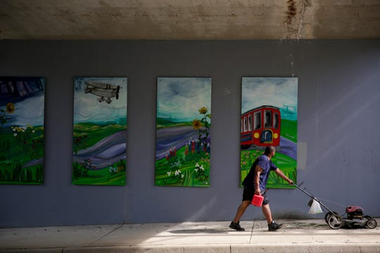 A man pauses as he walks past four of the eight panels on the new 18th st. underpass mural installation painted by the Mayor's Youth Council, Friday, June 7, 2019, in Lafayette.