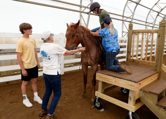 Elizabeth Burgoon gets on a horse with the help of Andrea Headly from the top of a mounting block Thursday afternoon, June 6, 2019, at the Home of Joy Farm in Pleasant Township. Will Custer, left, built two mounting blocks for the Fairfield County Special Olympics Equestrian team for his Eagle Scout project. Custer grandmother Mary Jelicka, second from left, is a volunteer with the team.