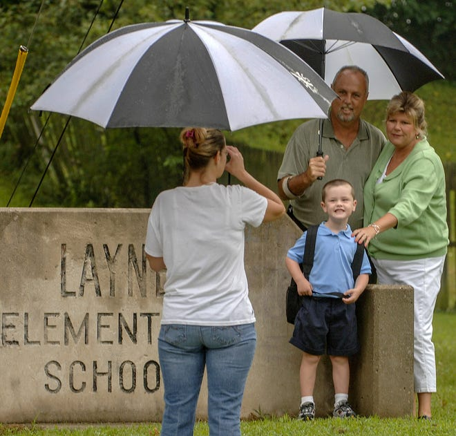 Devin Tucker, 5, grandparents Gayle and James Tucker, give their best smiles as his mother, Lynn Talley, left, takes their photo in front of the Layne Elementary School sign.  Devin is a kindergartener.