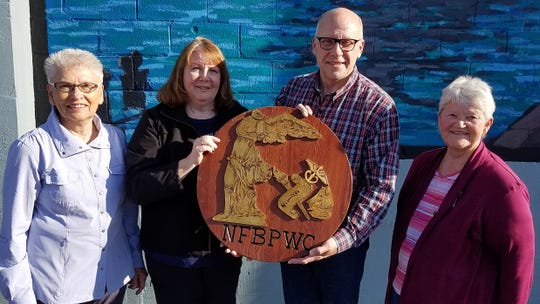 Lakeshore Business and Professional Women's group recently disbanded. Their emblem, hand-carved by Elsa Dramm in 1936 and proudly displayed at each meeting, was presented to Fritz Dramm, Elsa's great-nephew. Pictured from left: Carol Gruetzmacher, Lauretta Krcma-Olson, Fritz Dramm and Gert Bloedorn.