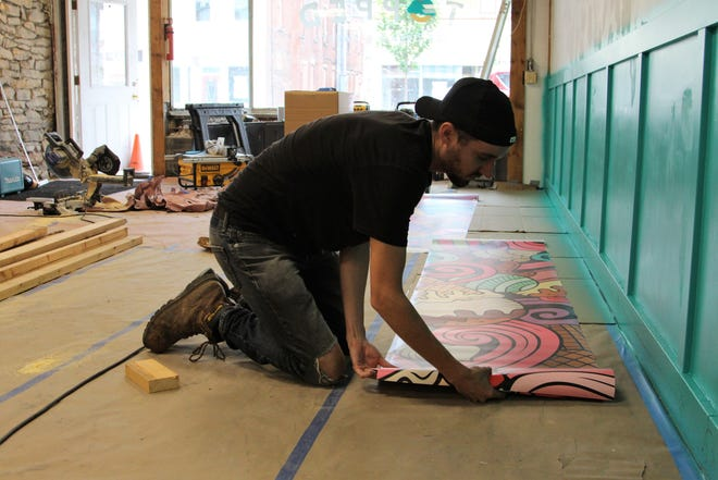 Alex Sheridan unrolls a section of wallpaper on Wednesday as he works to get a downtown Marion ice cream shop he part-owns ready for business by the end of the summer. It is one of a number of locations on South Main Street that he has been renovating over the year.