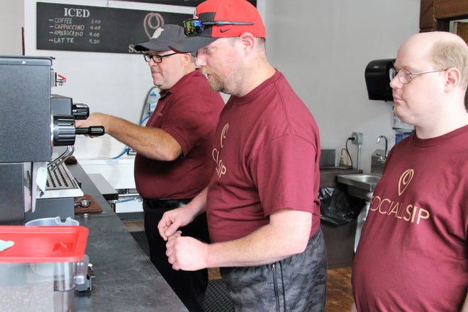 Manager Joel Hedrick inspects the equipment at Social Sip, a coffee shop that opened last month on North Prospect Street, as his employees Greg Dawson and Eric Craig watch Friday morning.