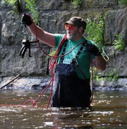 Jim Walters of West Bend uses a powerful magnet to go fishing for metal objects in the Milwaukee River in an  area below what was once a railroad bridge but is now part of a recreational trail. Walters pulls 4 railroad spikes from beneath what was once a railroad bridge with one cast.