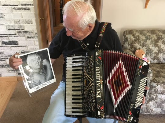 Glenn L. Schmidt holds the signed photo and one of his accordions. He got the photo signed after playing the Beer Barrel Polka for Da Crusher.