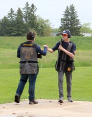 Landon Bartolomei, left, and Oscar Pruhs share a fist bump between stations at the 2019 Southeast Wisconsin Youth Traphooting Conference Championships at Waukesha Gun Club. The boys are members of the Marquette University High School Trap Team.
