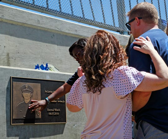 Family, friends and colleagues of the late Milwaukee Police Officer Charles Irvine Jr. gather at the unveiling of a plaque on the North 76th Street bridge over West Silver Spring Drive, where Irvine was killed a year ago in a crash during a pursuit.