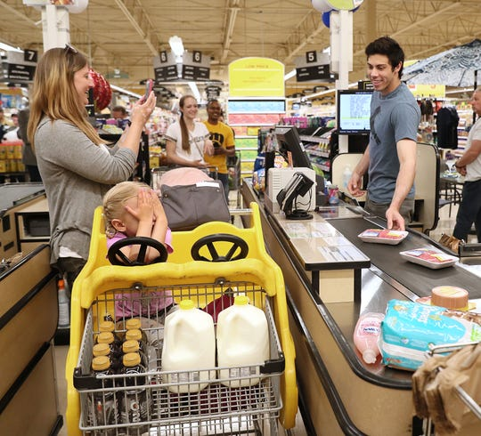 As part of the Brewers' #KindnessInMKE event, Christian Yelich checks out and buys groceries for Kristin Matz of West Milwaukee her daughter Kaylee.