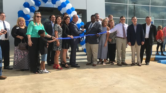 Rick Flick, owner/dealer of Banner Automotive Group, cuts a ribbon at the new Banner Ford of Monroe.