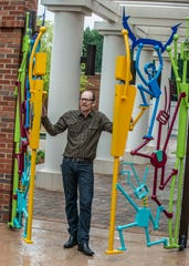 Montgomery artist Vincent Buwalda stands between the doors of his artwork, The Children's Gate. The Montgomery Museum of Fine Arts unveiled The Children's Gate on Thursday, June 6, 2019