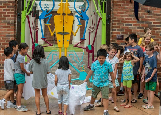 Art camp kids pull the sheet off the colorful robot figures of The Children's Gate. The Montgomery Museum of Fine Arts unveiled The Children's Gate on Thursday, June 6, 2019