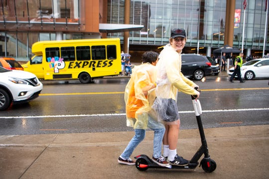 People ride scooters in the rain during the CMA Music Festival on June 7, 2019, in Nashville.