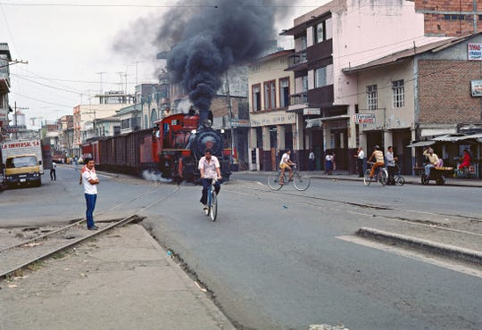 Ecuador, 1988: Guayaquil & Quito locomotive No. 11, built by Philadelphia's Baldwin Locomotive Works in 1990, steams right through the middle of Milagro, Ecuador, on its regular route.