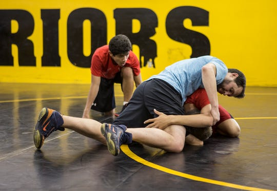 Victor Oliver watches as Aaron Martin, 2003 state champion works with Ryan Shull on his technique. Martin returned to his Alma Mater for three days to help with the wrestling camp.