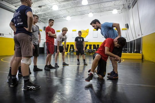 Aaron Martin, 2003 state champion demonstrates a move with the help of Victor Oliver during a wrestling camp at Watkins High School. Martin returned to his Alma Mater for three days to help with the wrestling camp.