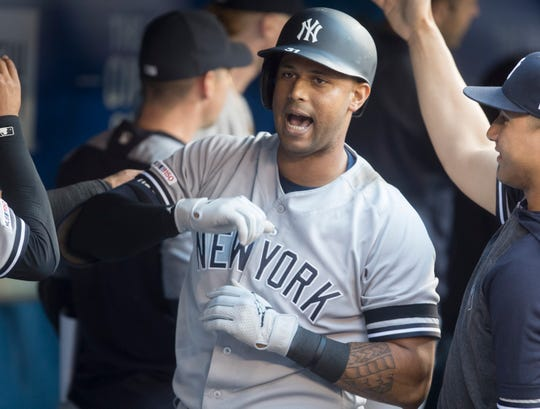 New York Yankees' Aaron Hicks is greeted in the dugout after hitting a three-run home run against the Toronto Blue Jays during the second inning of a baseball game Thursday, June 6, 2019, in Toronto. (Fred Thornhill/The Canadian Press via AP)