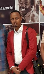 Abdikadir Mohamed poses at an airport in South Africa before boarding his flight to U.S.