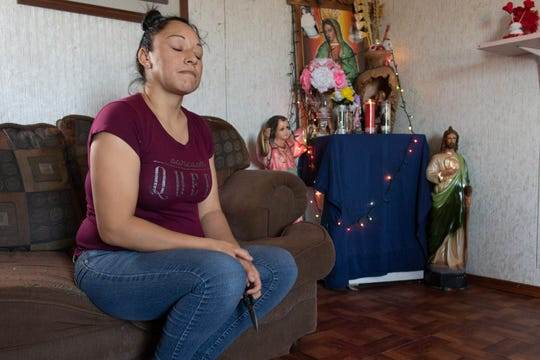 Virginia B. sits in her home beside her photo of the Virgin of Guadalupe and her San Judas statue.