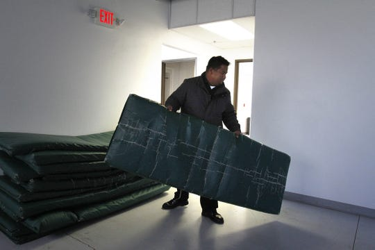 Bill Simon with the Salvation Army pulls out a sleeping mat, Friday, Nov. 6, 2014, at The Roof in Farmington.