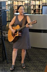 Singer-songwriter Jill Cohn strums her guitar during her show on Friday at the Farmington Public Library.