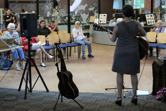 Members of the audience applaud as Jill Cohn finishes a song during the opening performance of the Farmington Public Library's annual Cottonwood Concert Series on Friday.