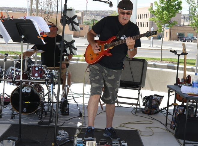 Jose Villarreal plays guitar for Mad Dog 20/20 while Doug Hodges plays the drums, Friday, June 7, 2019, during TGIF at the Farmington Civic Center.