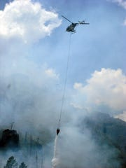 A helicopter drops fire retardant on a blaze at Bandelier National Monument in New Mexico in 2009.