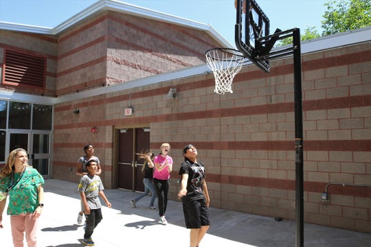 Boys and Girls Club of Farmington Director of Development Nikki Taylor, left, watches as teens play basketball on the outdoor patio of the new John Oliphant Taco Bell Teen Center on June 6.