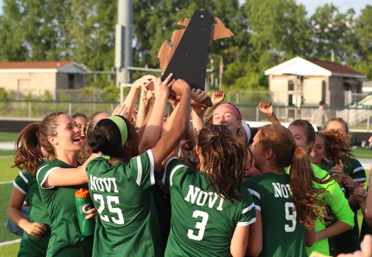 Novi's soccer team celebrates after winning the regional championship.