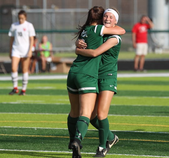 Novi's Avery Fenchel (right) hugs a teammate after scoring a goal against Grand Blanc.