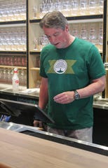 Bartender Jim DeMarrow rings up a customer at the new Arbor Brewing taproom in Plymouth.