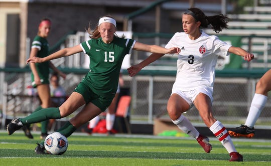 Novi's Avery Fenchel dribbles past Grand Blanc's Ally Childers.