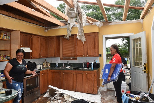 Red Cross worker Star Rollins, right, arrives at the Guilbeau residence Friday on Mills Road near Sunset with supplies after a storm ripped the roof of the home Thursday. Laura Guilbeau is shown cleaning debris.